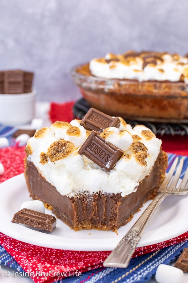 A white plate with a slice of chocolate s'mores pie topped with marshmallow mousse and toasted marshmallows with a bite take out of the pie.