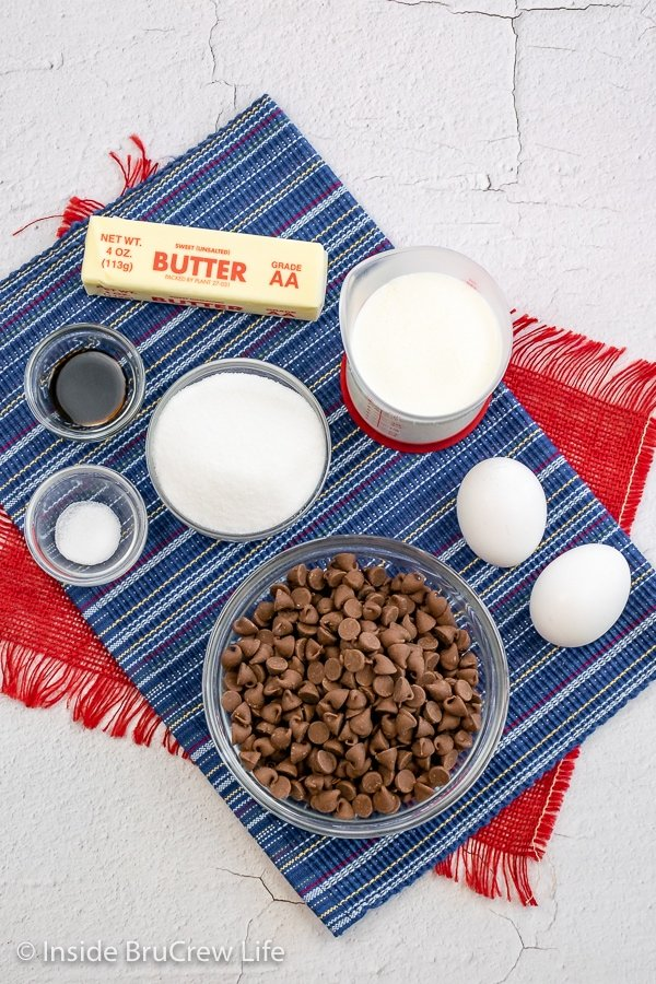White board with bowls of ingredients to make a S'mores Pie.