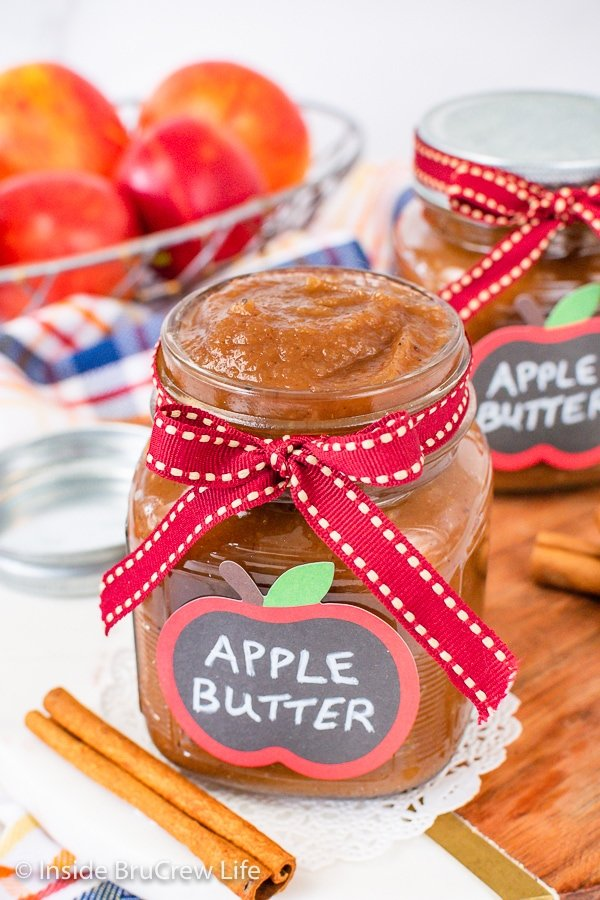 Two clear jars with ribbons and labels filled with homemade apple butter.
