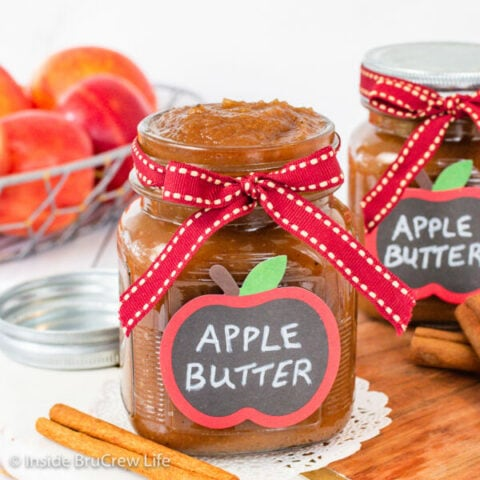 A clear jar with a ribbon and label filled with traditional apple butter.