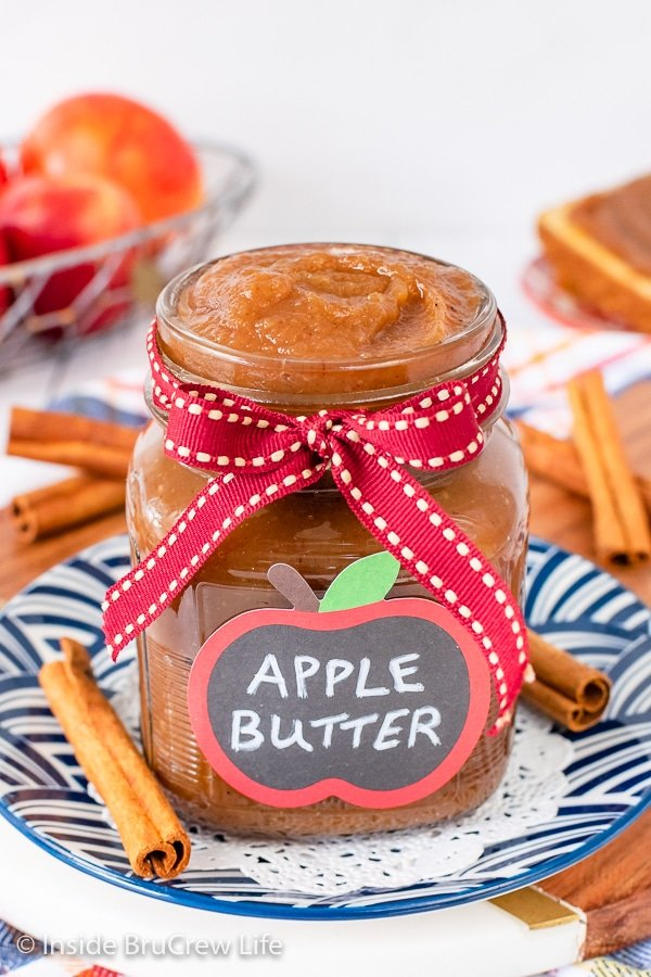A clear jar with a ribbon and label filled with smooth homemade apple butter.