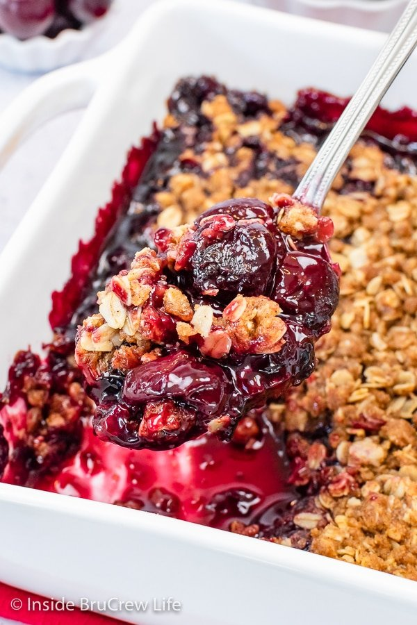 A white baking dish filled with cherry crisp and a spoon lifting some out.