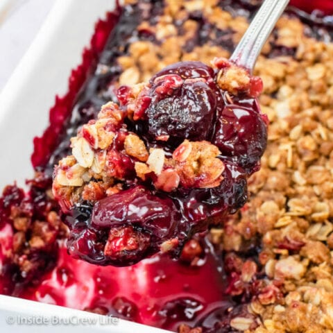 A spoon lifting up a scoop of cherry crisp out of a pan.