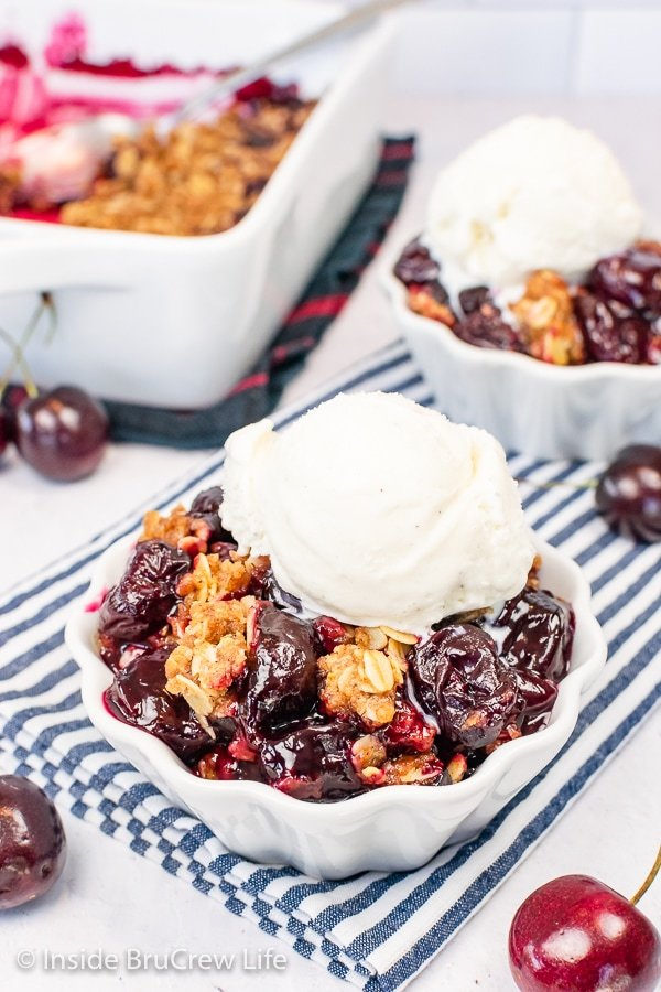 Two white bowls filled with cherry crisp and topped with a scoop of vanilla ice cream.