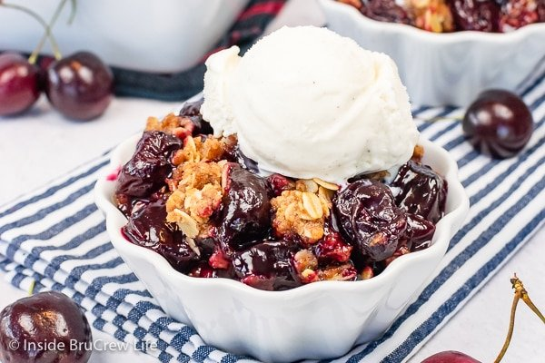 A white bowl filled with cherry crisp and vanilla ice cream.