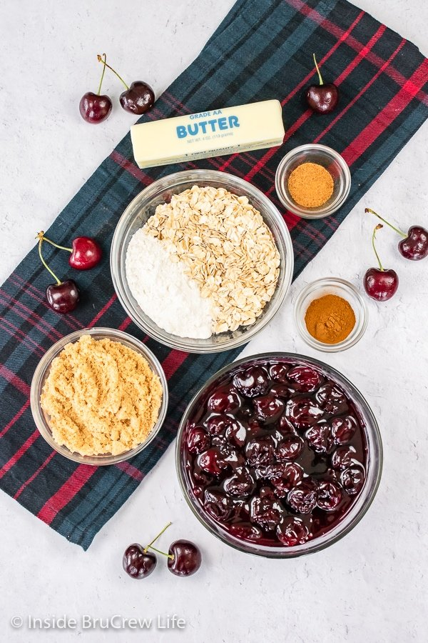 A white board with bowls of ingredients to make cherry crisp on it.