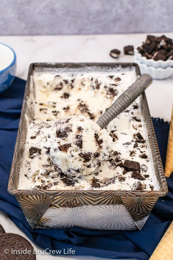 A metal pan filled with cookie cream ice cream and an ice cream scoop sitting on top.
