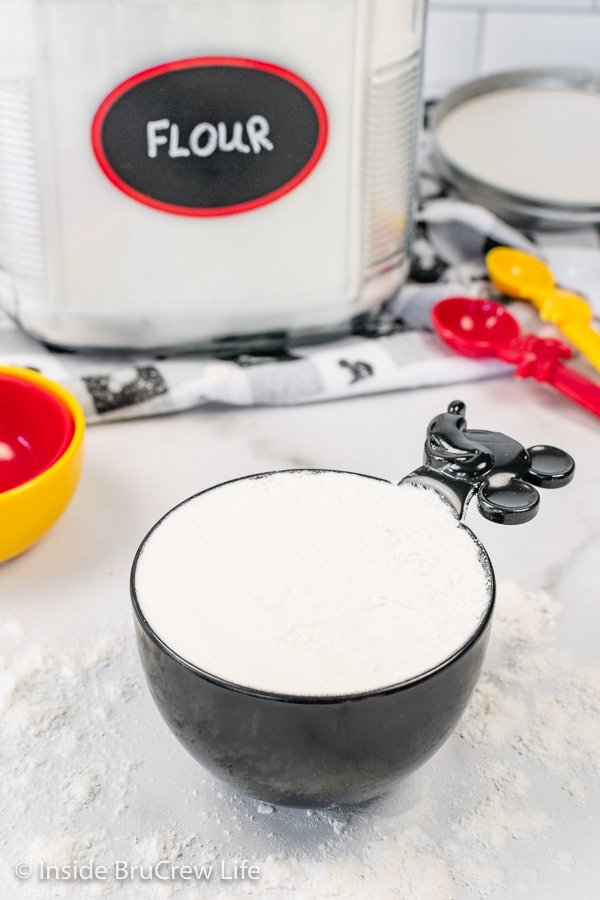 A black measuring cup filled with leveled flour.