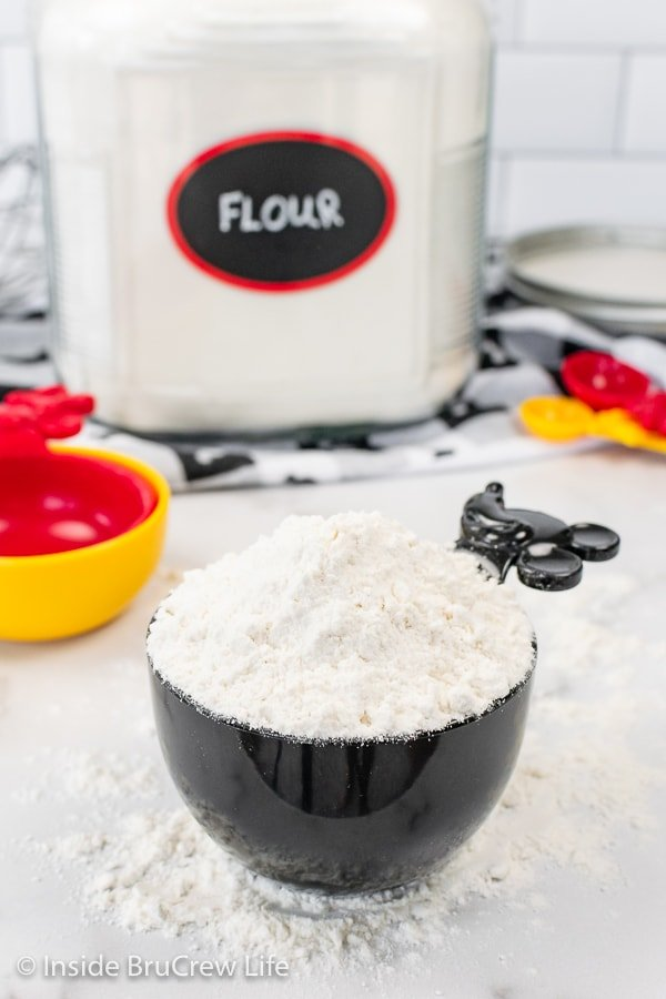 A black measuring cup with a mounded hill of flour on top and a flour container behind it.