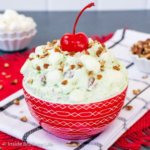 A red bowl filled with green pistachio fluff salad.