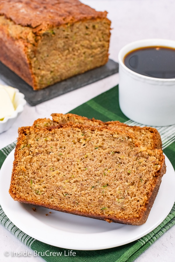 A white plate with two slices of zucchini bread with banana on it.