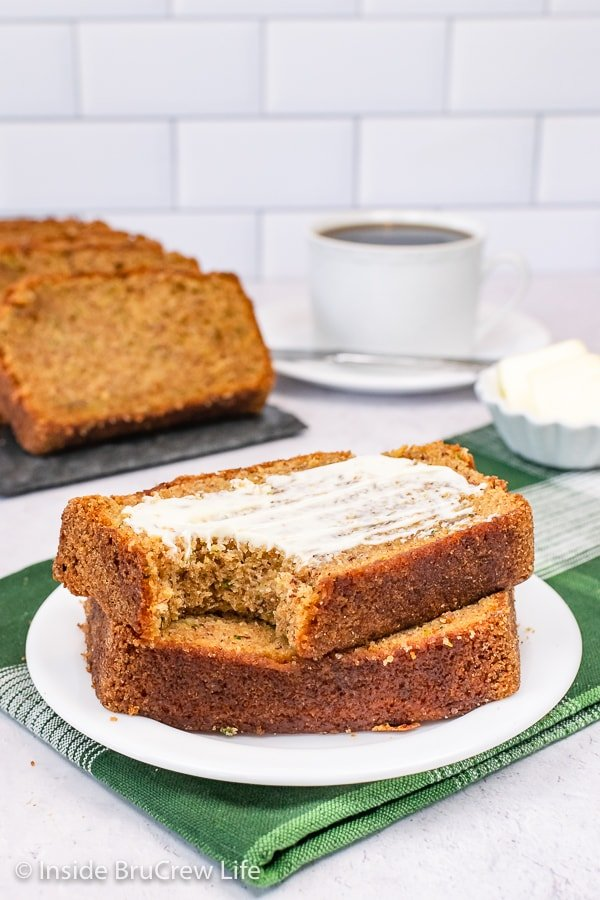 A white plate with two slices of zucchini bread on it. Butter is spread on the top slice.