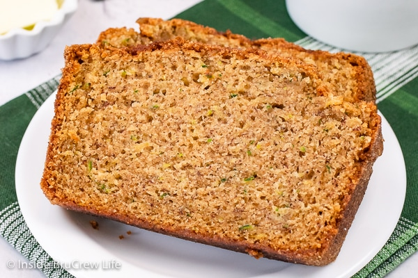 A white plate with two slices of zucchini bread on it.