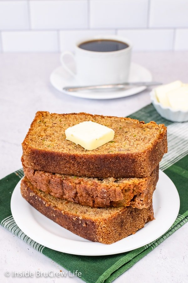 Three slices of zucchini banana bread stacked on a white plate with a slice of butter on top.