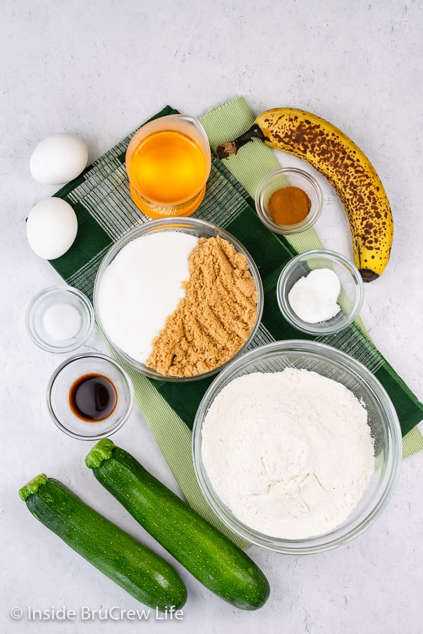 A white board with bowls of ingredients to make a zucchini banana cake on it.