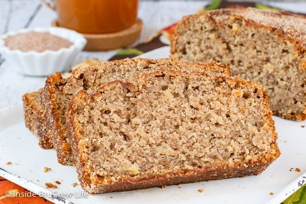 Slices of apple cider bread lying on a white tray.
