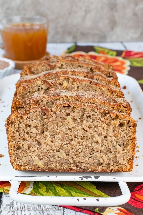 Slices of cinnamon sugar topped apple cider bread on a white tray.