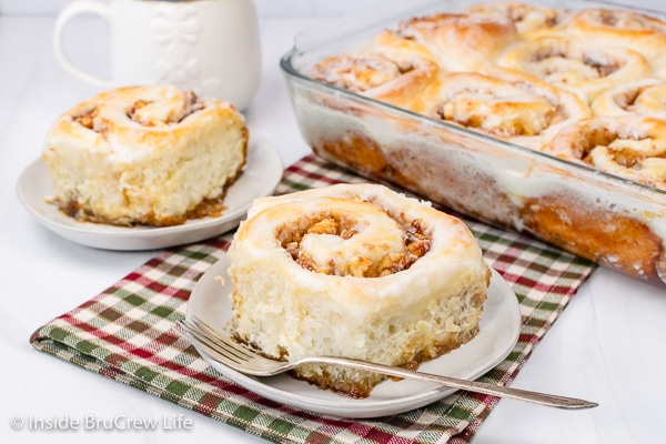 Two white plates with homemade apple cinnamon rolls on them.