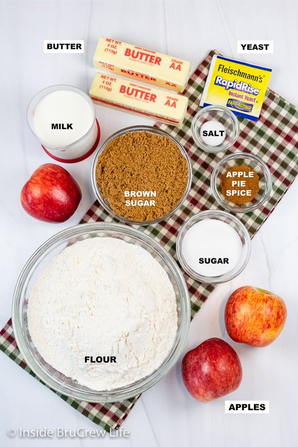 Overhead picture of a white board with bowls of ingredients to make easy apple cinnamon rolls.