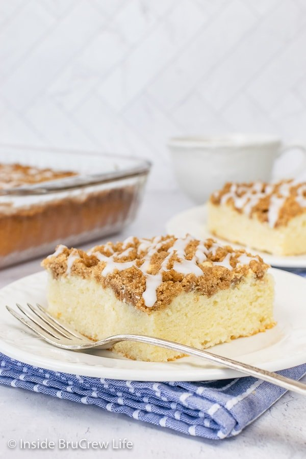 Two white plates with pieces of easy coffee cake drizzled with a sweet glaze.