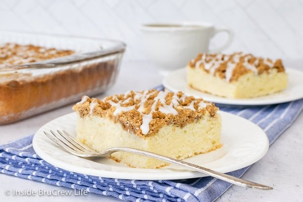 Two white plates with squares of coffee cake with brown sugar crumbles and glaze.