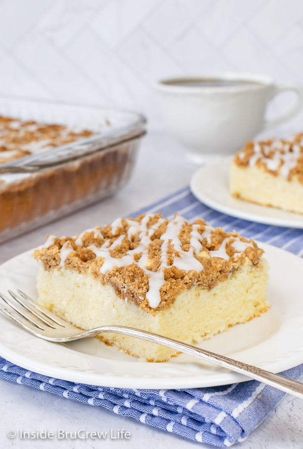 A white plate with a fork and a square of sour cream coffee cake with brown sugar topping and glaze.