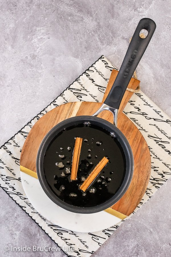 Overhead picture of a saucepan with maple syrup and cinnamon sticks in it.
