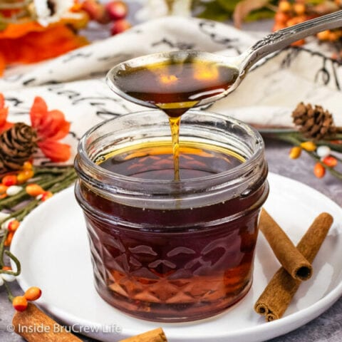 A clear mason jar filled with cinnamon syrup with a spoon drizzling some down into it.