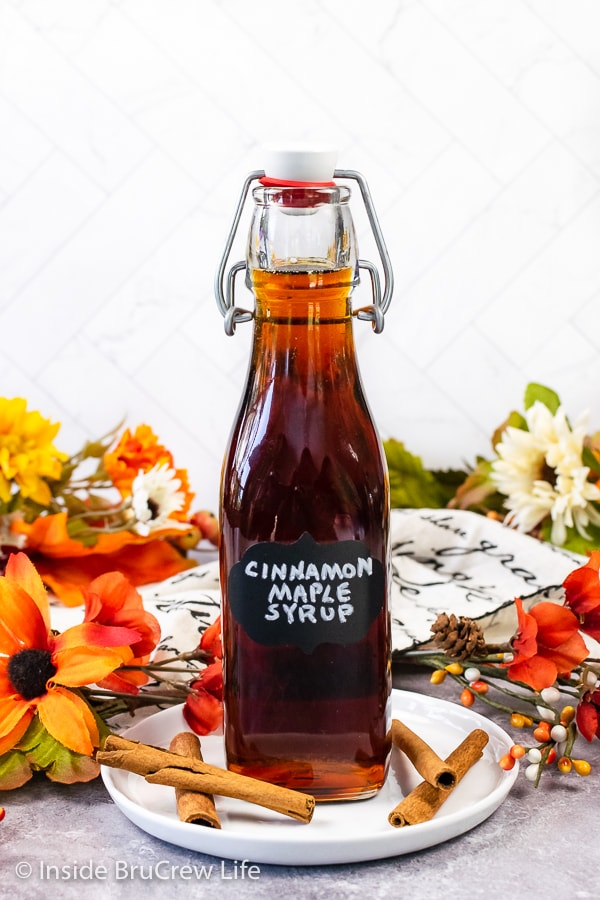 A clear bottle filled with Cinnamon Maple Syrup with a black label on it.