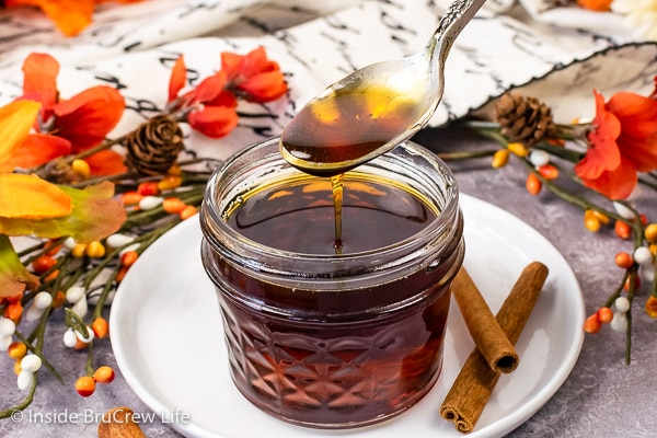 A clear jar on a white plate filled with cinnamon pancake syrup with a spoonful of syrup being poured in.